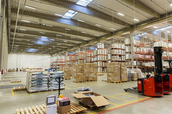 logistic, storage, shipment, industry and manufacturing concept - forklift loader and cargo boxes storing at warehouse